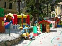 Ecco l'area giochi esterna con gli scivoli e le casette di plastica.